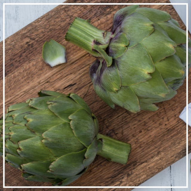 Artichokes from the garden on wooden chopping board