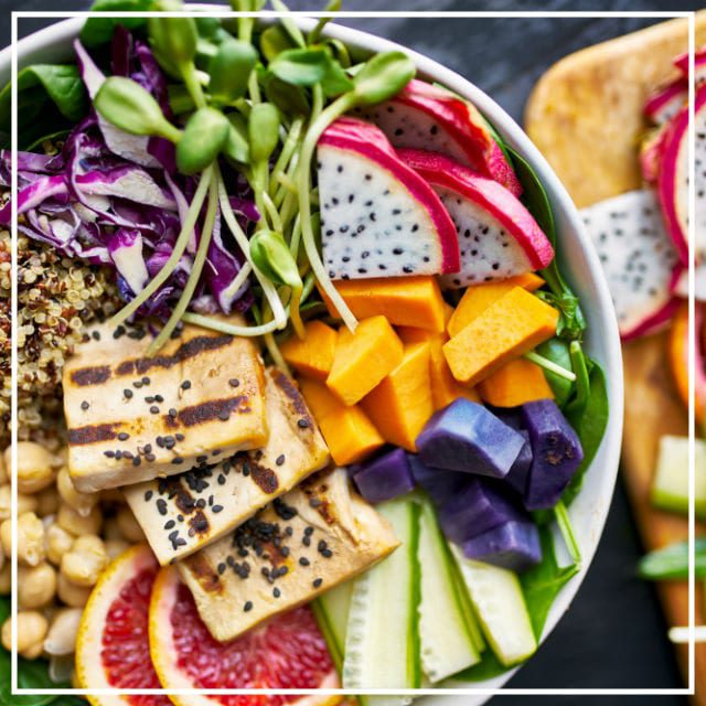 Large white bowl of sliced fresh fruits with grilled tofu